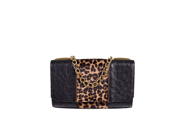 Front view top flap clutch bag. Black ostrich and printed hair on hide clutch with gold leather trim. Top chain handle in 24 carat gold plated decorative hardware. Detachable shoulder strap from chain and leather. Inside back zipper pocket and pocket. Suede leather lining and hidden magnetic lock