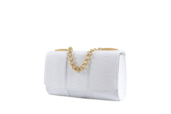 Side front view Belinda white ostrich shin top flap clutch bag from the Adele Exclusive Luxury Design Handbag Collection with top chain handle and decorative hardware, 24 carat gold plated. Chain and leather detachable shoulder strap. Inside back zipper pocket and front inside patch pocket. High quality suede leather interior and hidden magnetic lock closure.