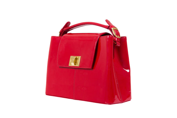 Front side view patent leather bag constructed fold over flap with turn lock closure. Adjustable handles decorated with a buckle and gold hardware. Internal zip pocket, two internal patch pockets and a zipper middle pocket. Detachable shoulder strap. High quality red suede leather interior. Bag feet studs.