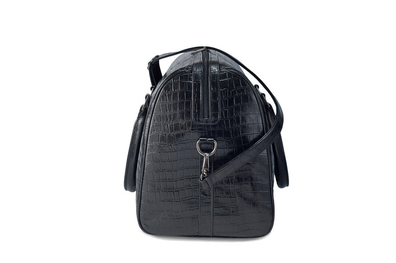 Side view Chris Embossed Crocodile Leather duffel bag. Double zipper and double carry handle, gun metal hardware. Adjustable detachable shoulder strap. Black suede leather interior, inside zip pocket and two open pockets.