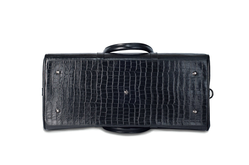 Bottom view Chris Embossed Crocodile Leather duffel bag. Double zipper and double carry handle, gun metal hardware. Adjustable detachable shoulder strap. Black suede leather interior, inside zip pocket and two open pockets.