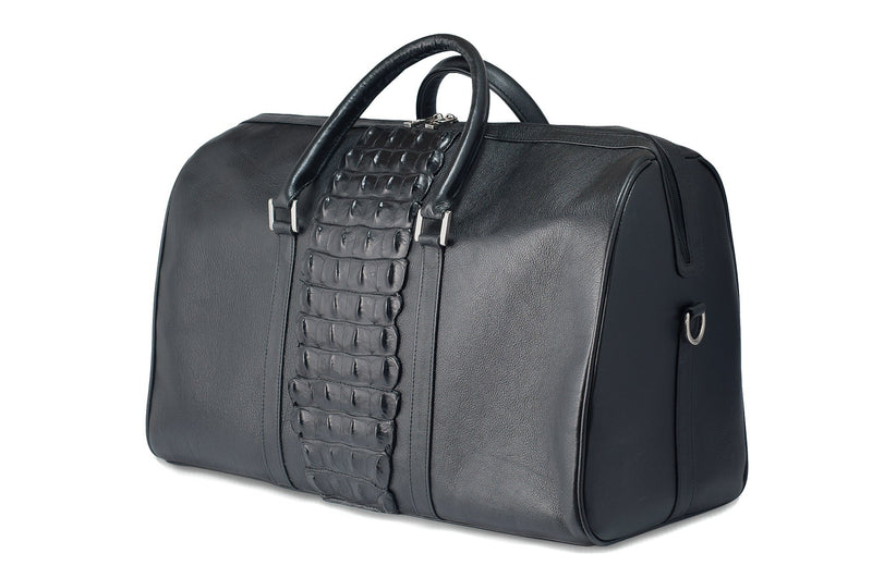 Side front view black bovine leather duffel bag crocodile tail insert. Double zipper, double carry handle, nickel hardware. Adjustable detachable shoulder strap. Black cotton twill interior, inside zip pocket, two open pockets.