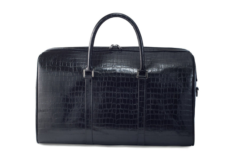 Front view Chris Embossed Crocodile Leather duffel bag. Double zipper and double carry handle, gun metal hardware. Adjustable detachable shoulder strap. Black suede leather interior, inside zip pocket and two open pockets.