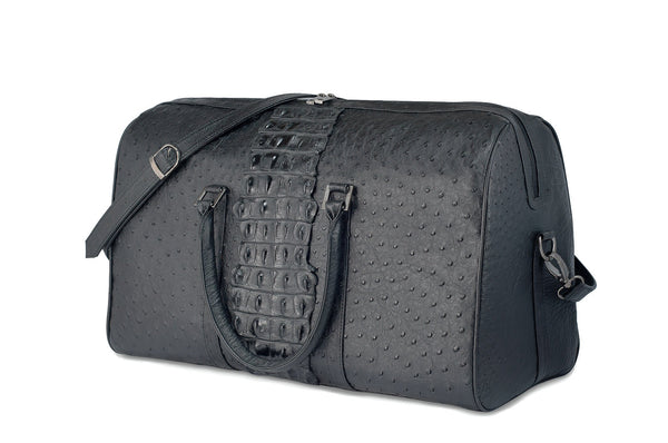 Front side view ostrich leather duffel bag crocodile tail insert. Double zipper, double carry handle, gunmetal hardware. Adjustable detachable shoulder strap. Black suede leather interior, inside zip pocket, two open pockets.