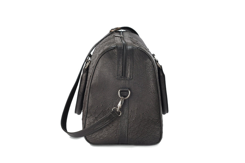 Side view black ostrich leather duffel bag. Double zipper and double carry handle, gun metal hardware. Adjustable detachable shoulder strap. Black suede leather interior, inside zip pocket and two open pockets.