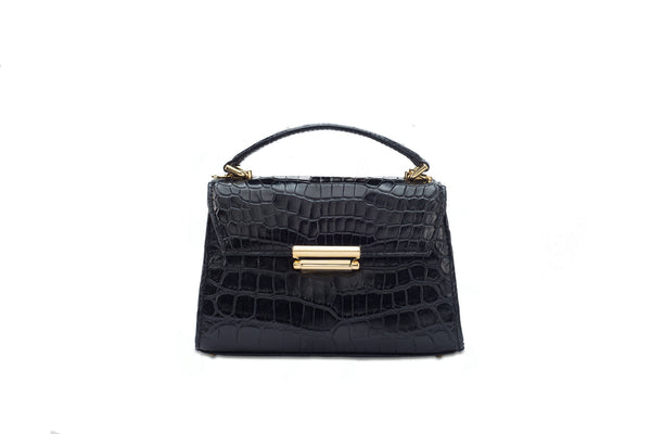 Front front view black crocodile leather constructed top flap handbag with press lock. Detachable adjustable shoulder strap. The bag contains an inside zipper with a back zip pocket. High quality black leather lining. Attached is a top handle with 24 carat gold plated fittings. The bottom panel features bag feet studs.