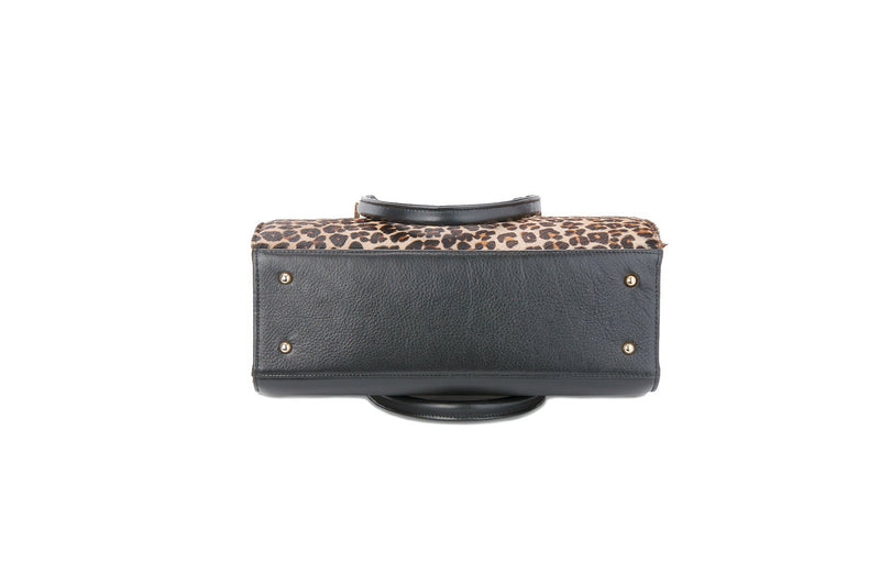 Bottom view Beverley. Black bovine leather side, back and bottom, with leopard printed hair on hide on the front panel. Contains an inside zipper with a back zip pocket. Bag interior consist of black high quality cotton lining. Top zip closure with gold plated fittings. Comes with a detachable shoulder strap with an adjustable buckle. Bottom panel features bag feet studs.