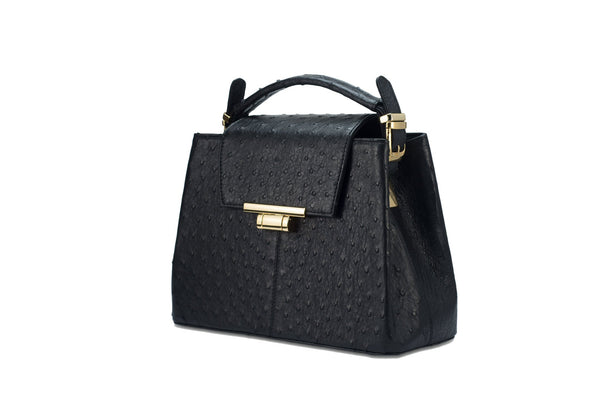 Front side view ostrich leather constructed top flap handbag with an Italian lift lock closure. Inside zipper pocket, leather suede interior. Top handle 24 carat gold plated hardware,detachable shoulder strap with adjustable buckle. Bottom feet studs.