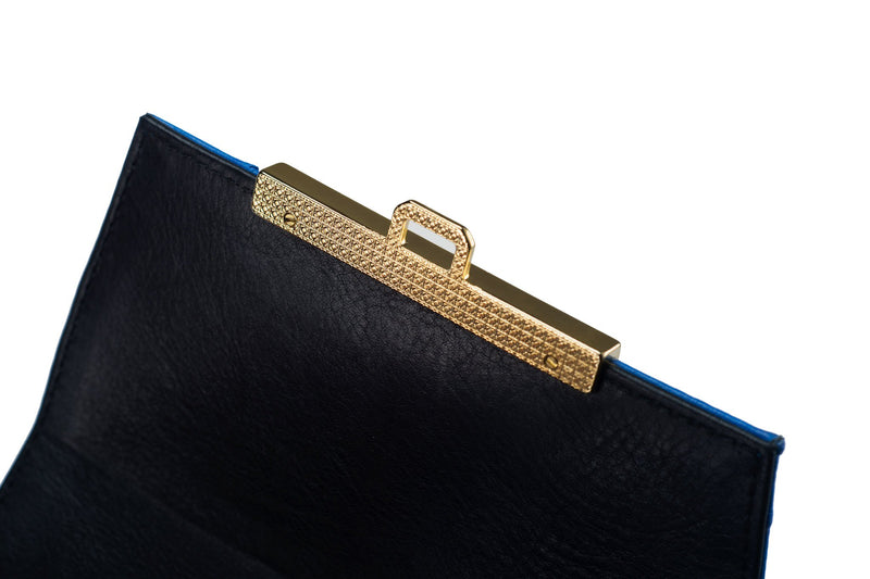 Top flap view ostrich leather constructed top flap handbag with an Italian lift lock closure. Inside zipper pocket, leather suede interior. Top handle 24 carat gold plated hardware,detachable shoulder strap with adjustable buckle. Bottom feet studs.