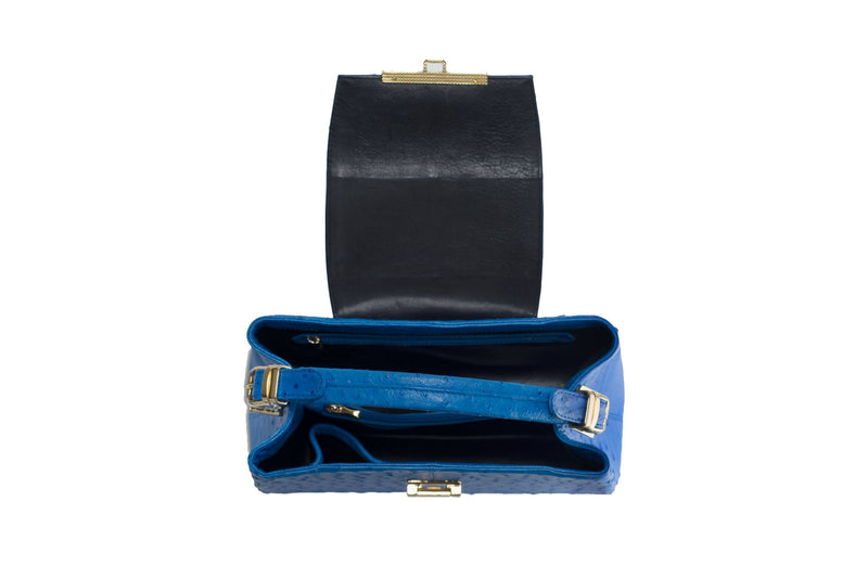 Open top view ostrich leather constructed top flap handbag with an Italian lift lock closure. Inside zipper pocket, leather suede interior. Top handle 24 carat gold plated hardware,detachable shoulder strap with adjustable buckle. Bottom feet studs.
