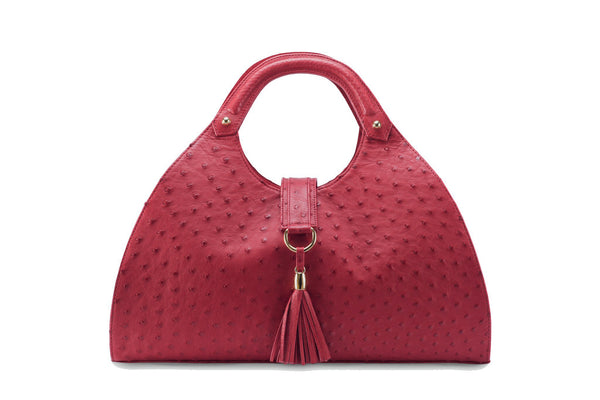 Front view Kimberley red ostrich Leather bag with fold over magnetic strap with D-ring & tassel decoration. Attached round shaped handles decorated with a studs.