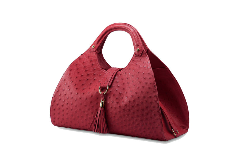 Front side view Kimberley red ostrich Leather bag with fold over magnetic strap with D-ring & tassel decoration. Attached round shaped handles decorated with a studs.