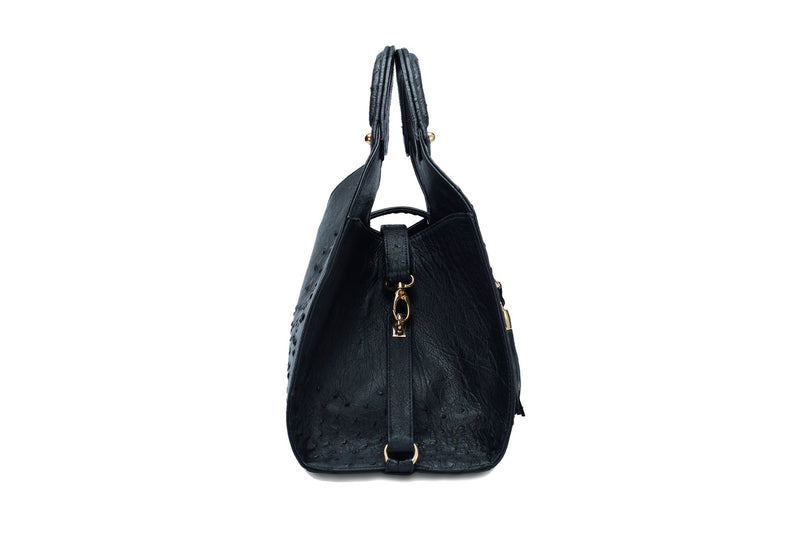 Side view Kimberley black ostrich Leather bag with fold over strap. Hidden magnet with D-ring & tassel decoration for closure. Attached round shaped handles decorated with a studs. Top snap hook closure internal zip pocket with two internal patch pockets. Black high quality suede leather lining, bag feet.