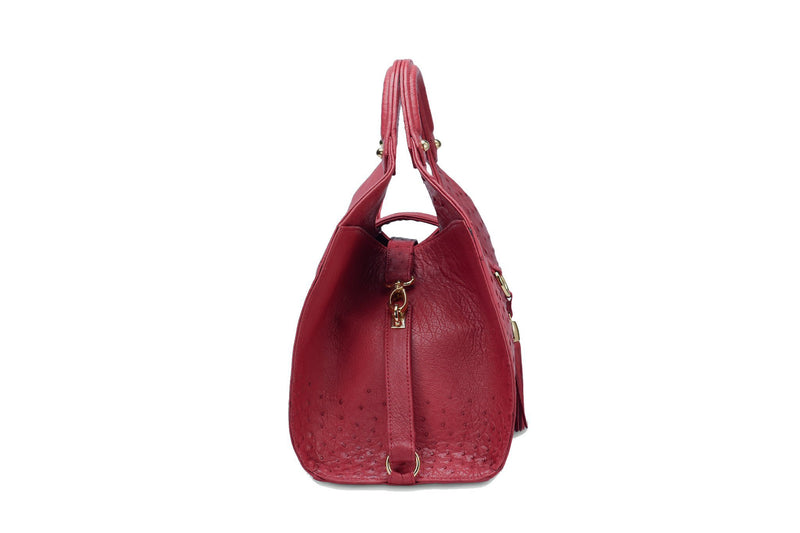 Side view Kimberley red ostrich Leather bag with fold over magnetic strap with D-ring & tassel decoration. Attached round shaped handles decorated with a studs.