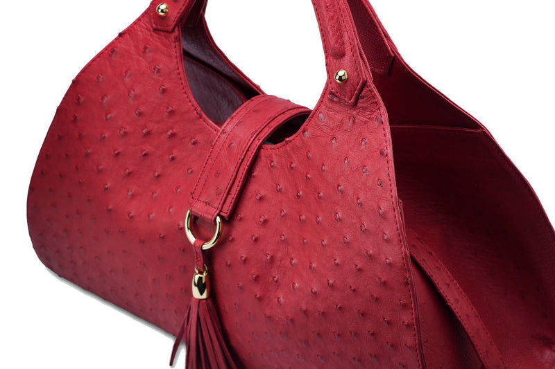 Top front side view Kimberley red ostrich Leather bag with fold over magnetic strap with D-ring & tassel decoration. Attached round shaped handles decorated with a studs.