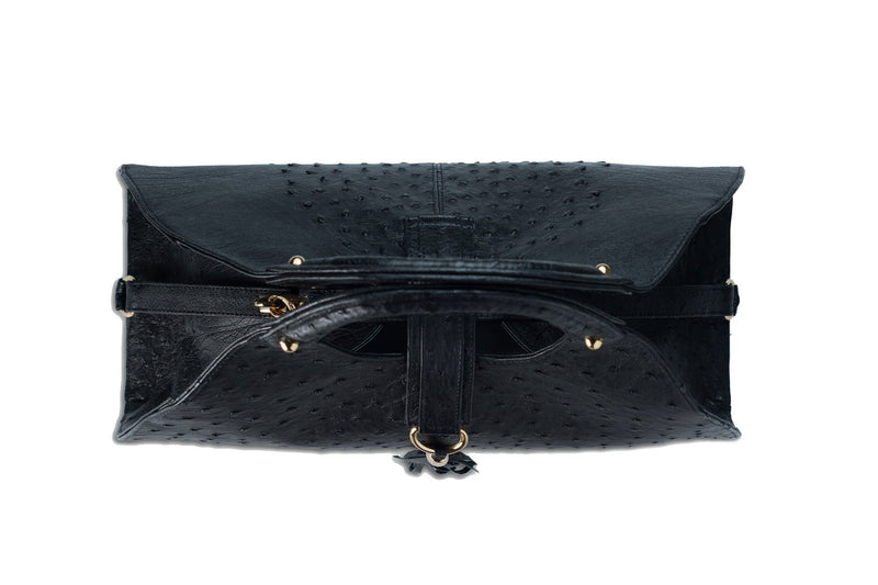 Top view Kimberley black ostrich Leather bag with fold over strap. Hidden magnet with D-ring & tassel decoration for closure. Attached round shaped handles decorated with a studs. Top snap hook closure internal zip pocket with two internal patch pockets. Black high quality suede leather lining, bag feet.