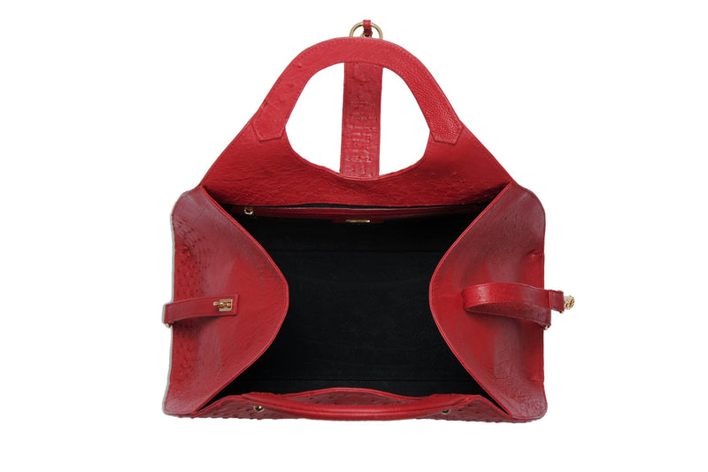 Top open view Kimberley red ostrich Leather bag with fold over magnetic strap with D-ring & tassel decoration. Attached round shaped handles decorated with a studs.