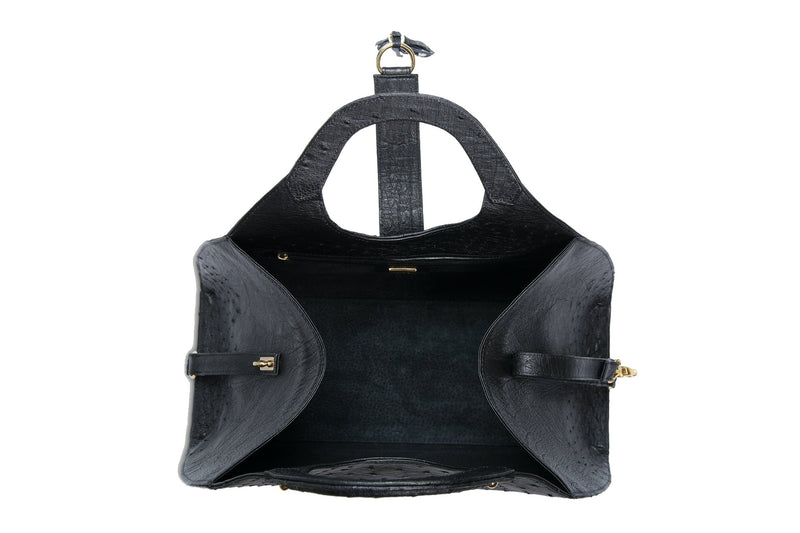 Top open view Kimberley black ostrich Leather bag with fold over strap. Hidden magnet with D-ring & tassel decoration for closure. Attached round shaped handles decorated with a studs. Top snap hook closure internal zip pocket with two internal patch pockets. Black high quality suede leather lining, bag feet.
