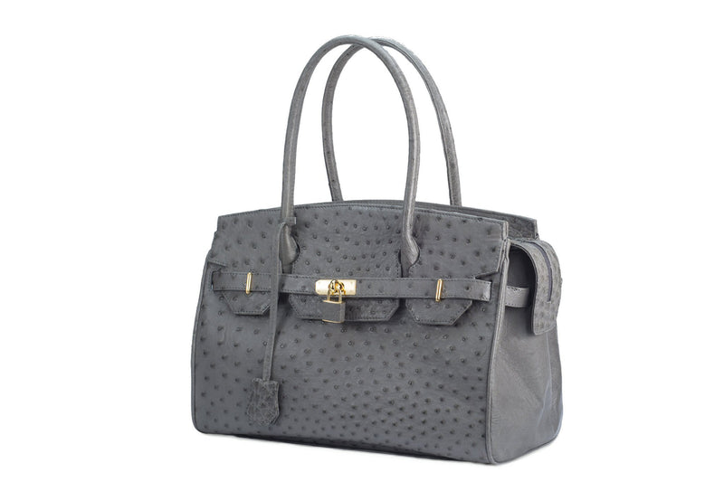 Ostrich leather bag with top zip. The interior contains an inside zip pocket with two internal patch pockets, and is lined with high quality black suede leather. Features a double handle and a gold lock system as decorative hardware. Bag feet studs are located on the bottom panel of the bag.