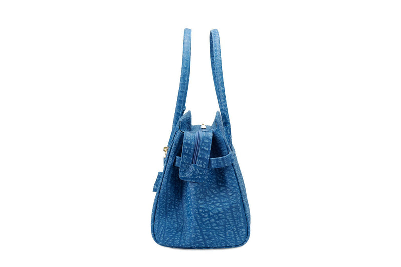 Side view Ripple buffalo blue leather handbag with top zip. The interior contains an inside zip pocket with two internal patch pockets, and is lined with high quality black suede leather. Features a double handle and a gold lock system as decorative hardware. Bag feet studs are located on the bottom panel of the bag.