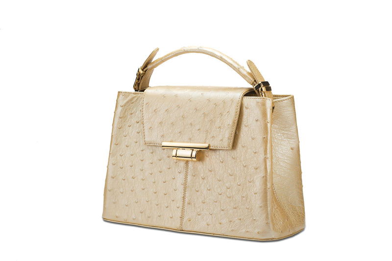 Side front view Ostrich leather constructed top flap handbag with an Italian lift lock closure. Inside zipper pocket, leather suede interior. Top handle 24 carat gold plated hardware,detachable shoulder strap with adjustable buckle. Bottom feet studs.