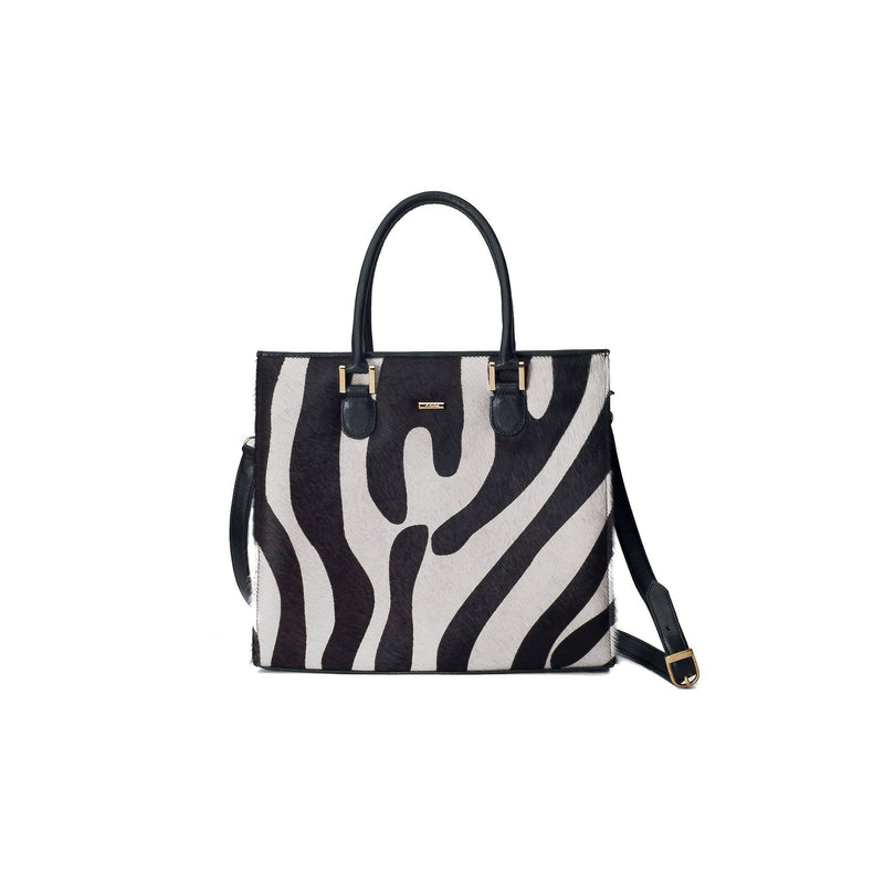 Linda front view with strap. Black bovine leather side, back and bottom panel, with white and black zebra printed hair on hide on the front panel. Contains an inside zipper with a back-zip pocket. The bag interior consists of high-quality black cotton suede lining. Includes a top zip closure with gold plated hardware, and a detachable shoulder strap with an adjustable buckle. Bag feet studs are located on the bottom panel.