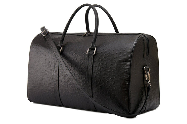 Side front view. Chris Leather duffel bag. Double zipper and an attached double carry handle. Adjustable and detachable shoulder strap. Black suede lines the bag interior. Inside zip pocket and two open pockets.