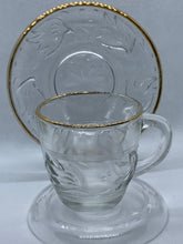 Load image into Gallery viewer, Unmarked.  Demitasse Cup and Saucer. Pressed Glass, Clear with leaves, gold trim.