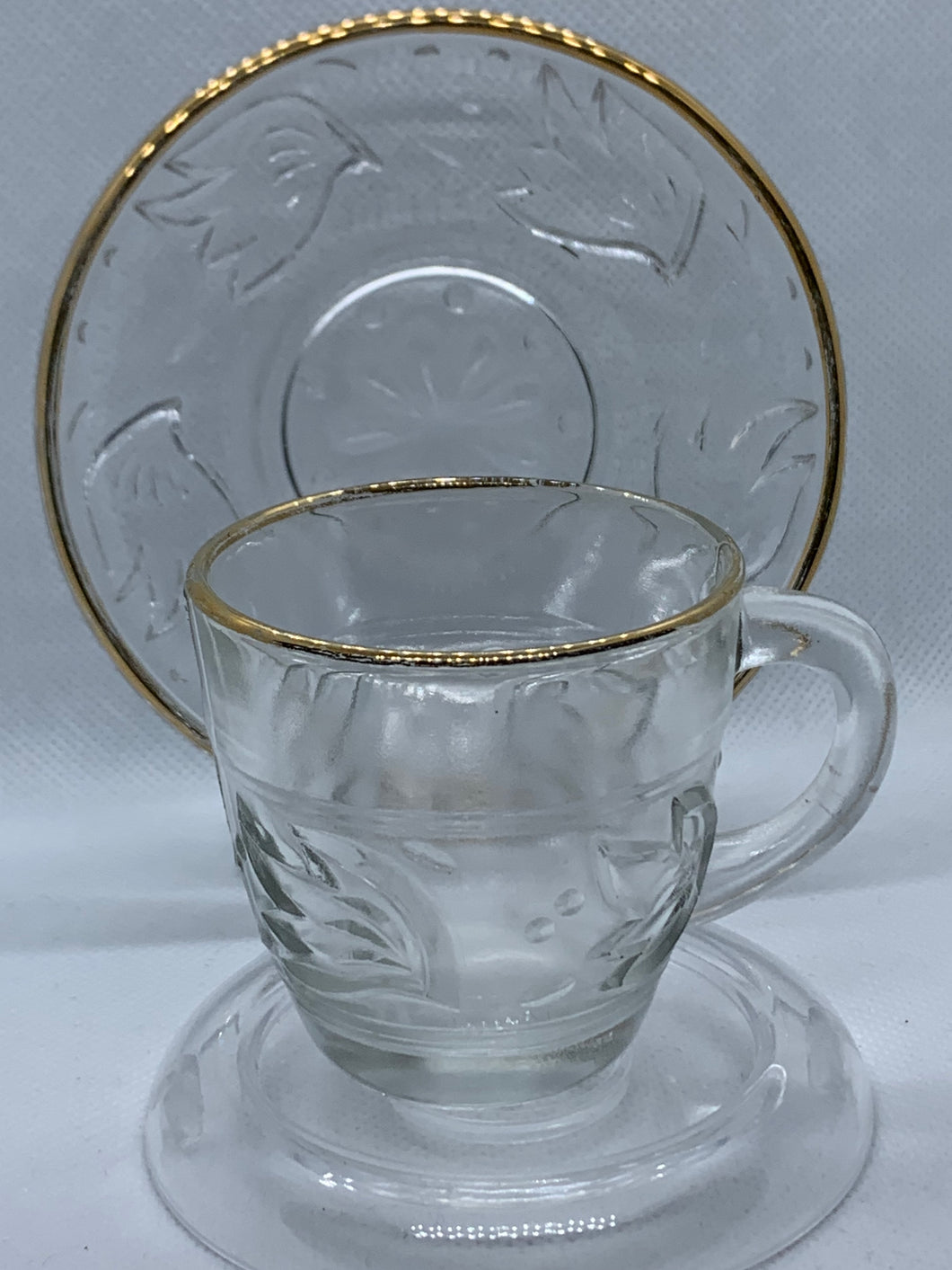 Unmarked.  Demitasse Cup and Saucer. Pressed Glass, Clear with leaves, gold trim.