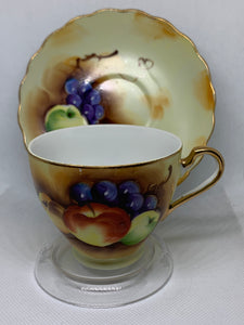 Japan, Cup and Saucer, mixed fruit on a pale yellow background