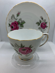 Delphine, England. Cup and Saucer.  Large pink rose, green and silver foliage.