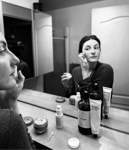 black and white image of a woman applying makeup in the mirror