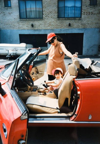 Pregnant mom and toddler daughter in red sports car