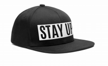 "An image of our black snapback with ""Stay Up"" embroidered on the front."