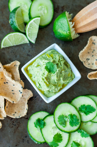 white bean dip with avocado and cilantro in a white bowl surrounded by limes