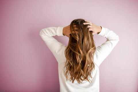 Long curly haired woman facing the pink and white wall, for Untangled