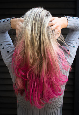 Woman with blonde and pink hair facing the black wall, for Untangled
