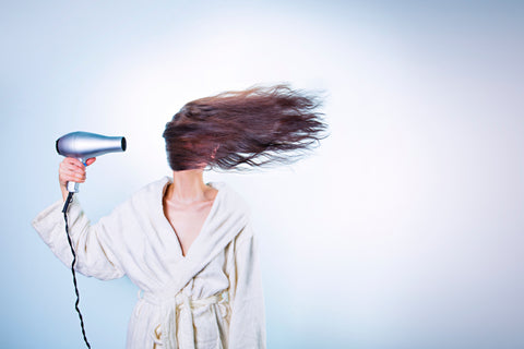 Woman in a bathrobe using a hair dryer, for Untangled