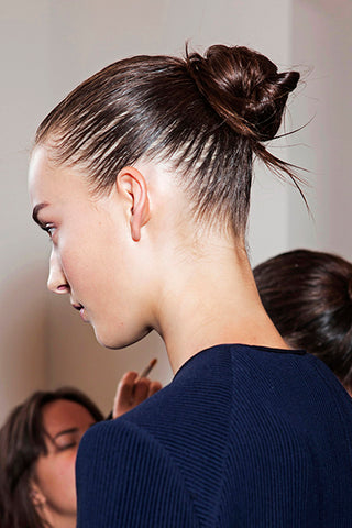 Lady sporting a bun with 2 people on the background, for Untangled