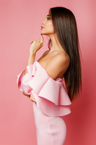 Woman with long straight hair wearing pink dress on pink background, for Untangled