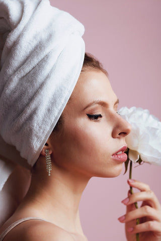 Woman with her hair wrapped in a towel while holding a flower close to her face, for Untangled