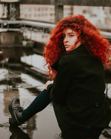 Curly redhead sitting on a wet street, for Untangled