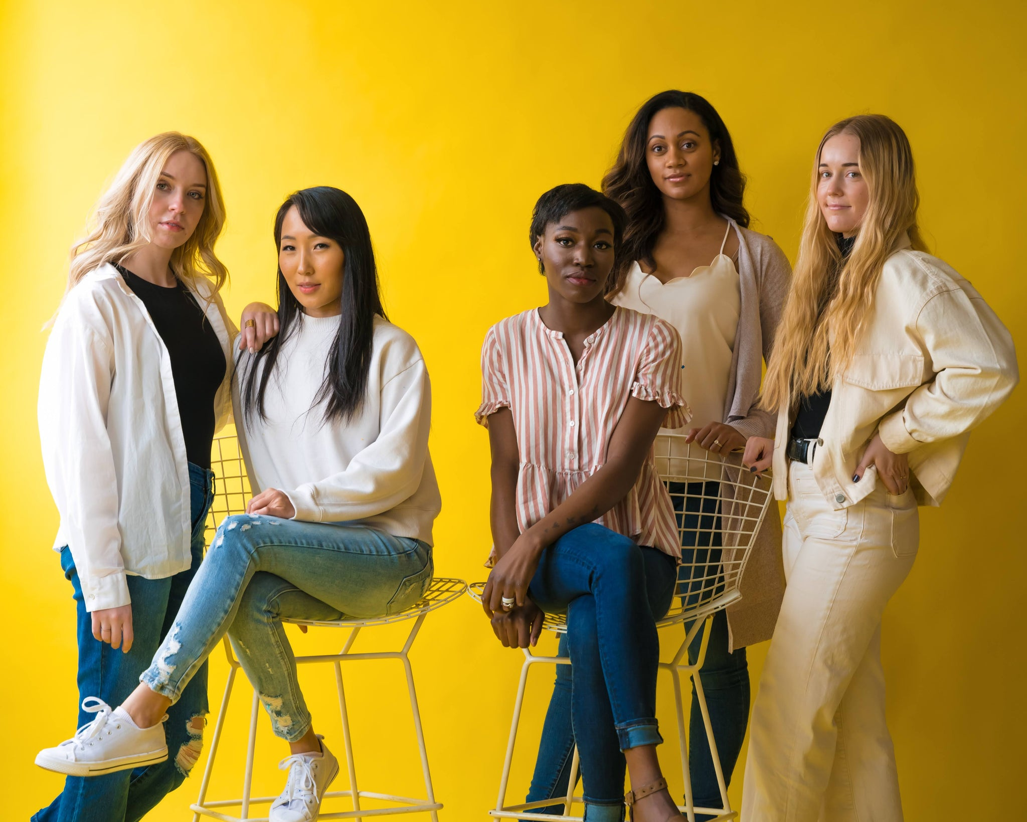 Group of women standing together in a power pose with a yellow background
