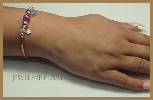 Rosegold  bracelet with shimmering balls and charms.
