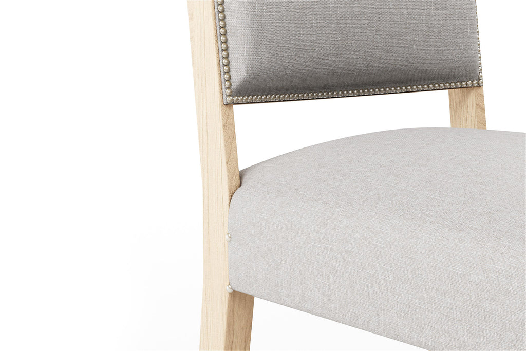 Dining room chair upholstered in light grey fabric.