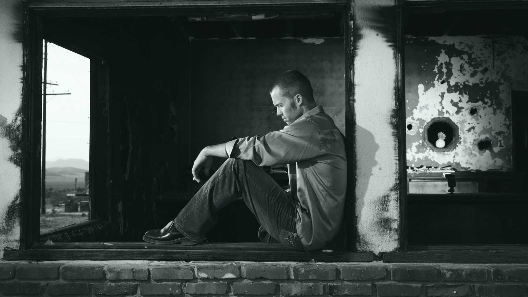 a man sitting against a pillar looking depressed to show how trying doesn't work