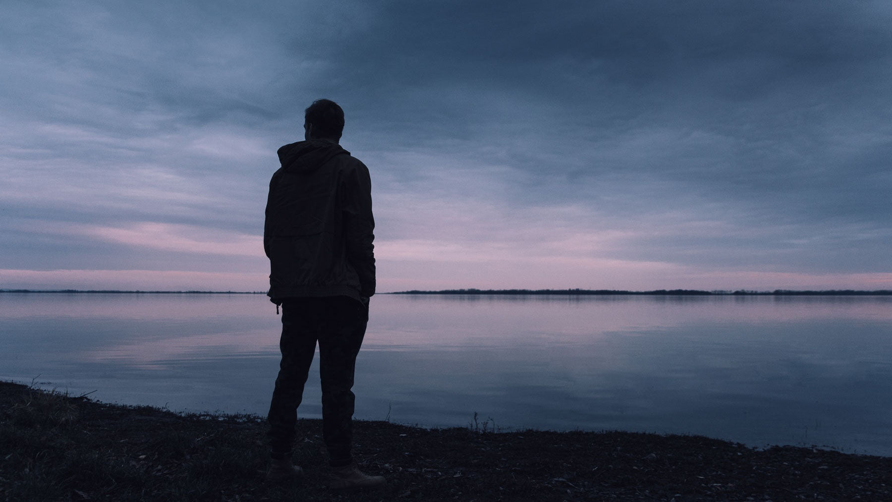 man looking sad at edge of lake