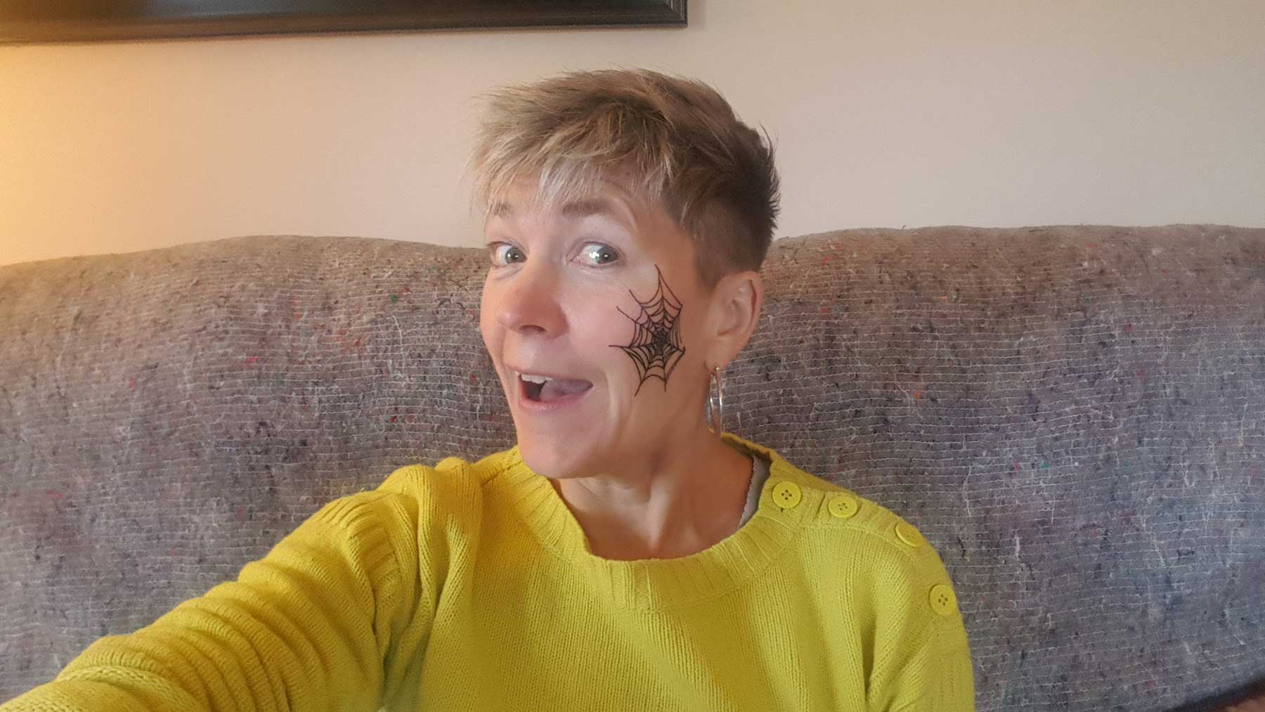 head shot of author with scary spider's web tattoo on her face to represent fear