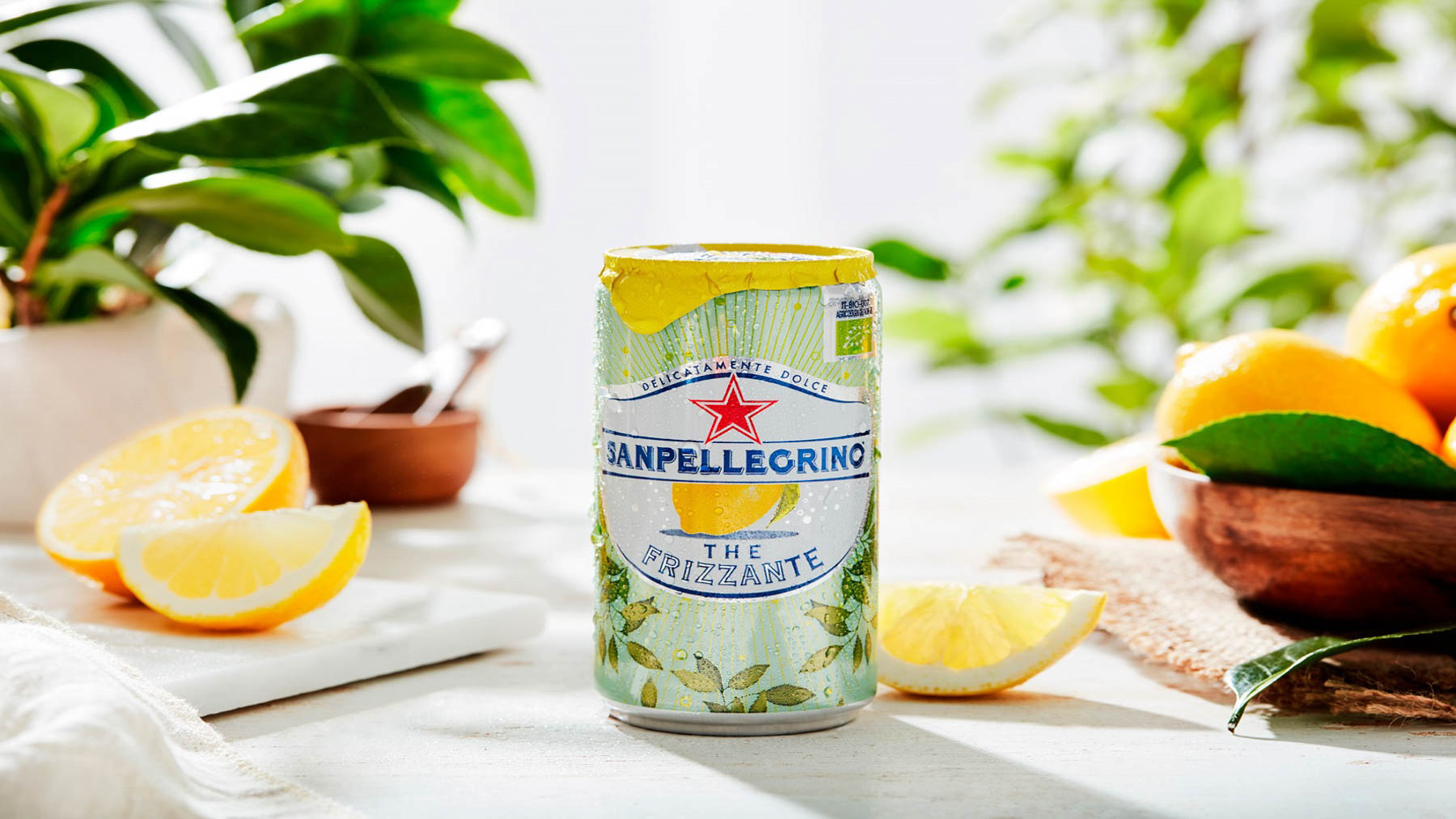 cold can of Pellegrino surrounded by fresh fruit