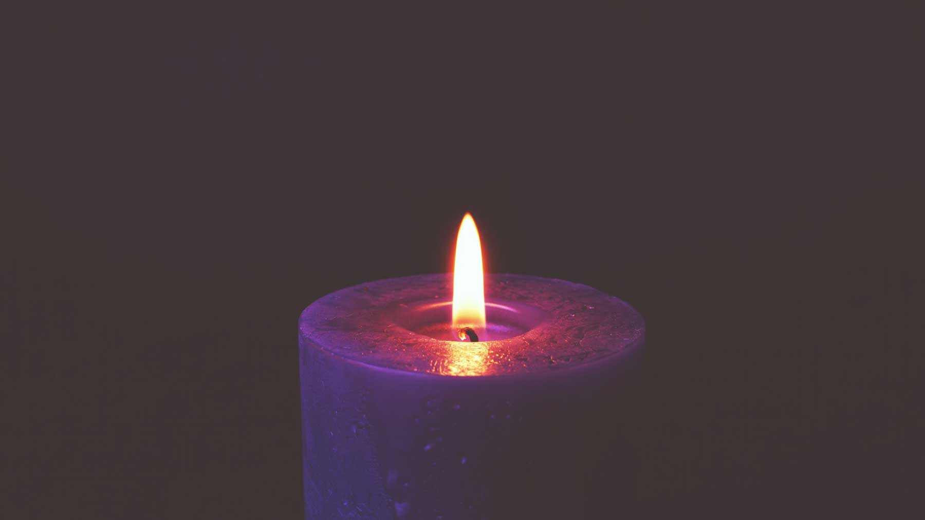purple candle and flame against a purple background to represent mindfulness and reflection